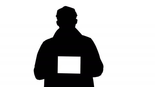 Silhouette Man in trench walking and holding tablet with white screen mockup presenting something.