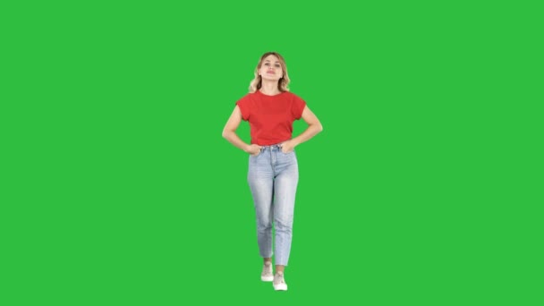 Blond woman walking with hands in her pockets and talking to camera on a Green Screen, Chroma Key.
