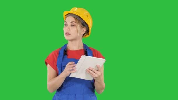 Ingenieurin überprüft Bauplan auf Touchpad und betrachtet Objekte, Gebäude um sie herum auf einem grünen Bildschirm, Chroma-Taste.