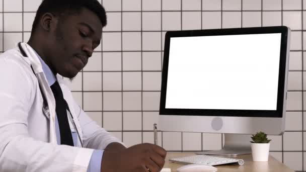 Young african doctor in a lab coat sitting in his office and taking some notes while looking at computer screen. White Display.