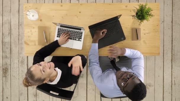 Horní pohled. Ženská a mužská pracovnice vzhlížejí a povídají si po profesionální střelbě v rozlišení 4K. 012. Můžete ji použít např. ve Vašem komerčním videu, lékařství, obchodu, prezentaci