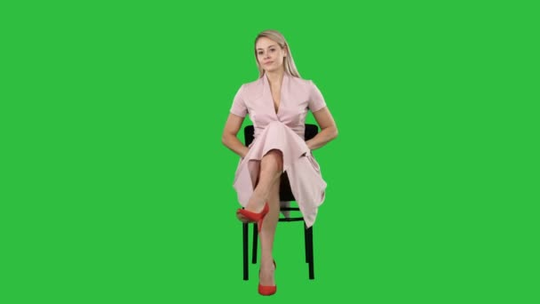 Beautiful young woman, girl, model blonde with long hair sitting on a chair and looking to camera on a Green Screen, Chroma Key.