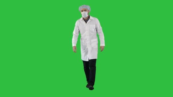 Fuß jungen männlichen Arzt in einer Maske und einem OP-Hauben auf einem Green-Screen, Chroma-Key