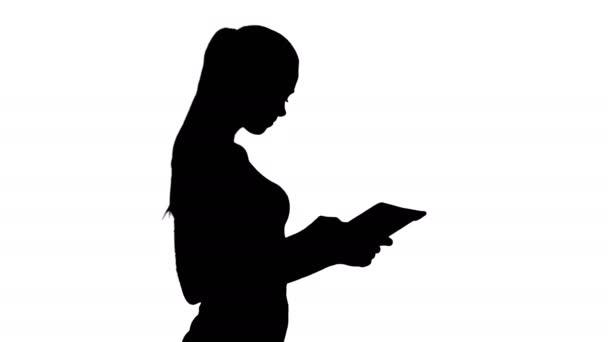 Střední rána. Boční pohled. Silueta Krásná mladá dospělá žena baví hraní hry s tabletem. Profesionální zásah v rozlišení 4K. 013. Můžete ji použít např. ve Vašem komerčním videu, podnikání