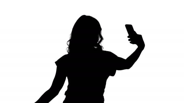 Silueta veselé ženské blogger nahrávání videa do předního fotoaparátu moderní telefon při chůzi.