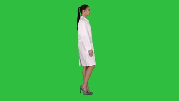 Ärztin Kosmetikerin im weißen Gewand läuft auf einem grünen Bildschirm, Chroma-Schlüssel.