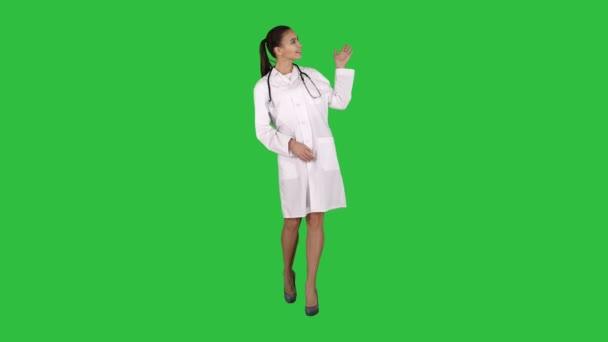 Mladý lékař žena prezentace a zobrazení produktu nebo text na zelené obrazovce, Chroma Key.