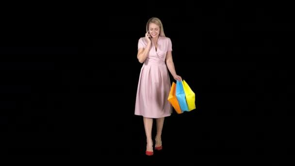 junge Frau beim Einkaufen und Telefonieren beim Gehen, Alpha-Kanal