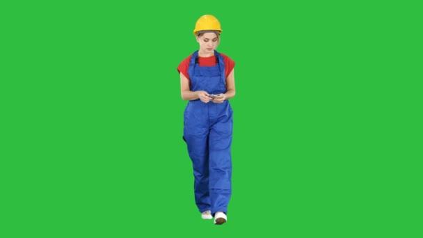 Ženské systémová stavební dělník počítání peněz při chůzi na zelené obrazovce, Chroma Key.