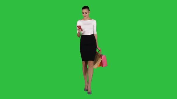 Šťastná mladá žena s smartphone takže obrázek své nákupní tašky na bílém pozadí.