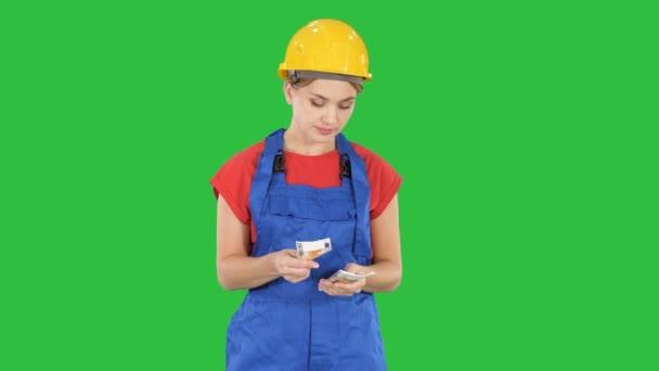 junge fröhliche Arbeiterin mit Gehaltsscheinen in Euro auf grünem Bildschirm, Chroma-Schlüssel.
