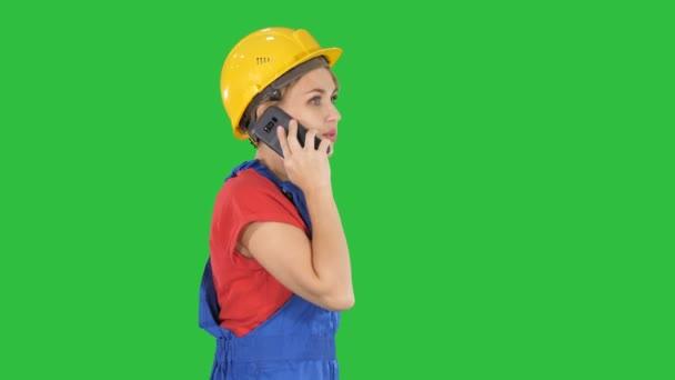 Krásné mladé tvůrce žena nosí žluté přilby volání na zelené obrazovce, Chroma Key.