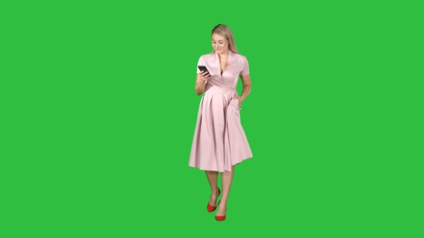 Young woman in pink looking at mobile smartphone and texting something while walking on a Green Screen, Chroma Key.