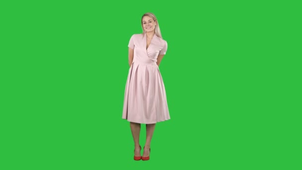 Porträt der Mode lächelnd junge schöne Frau Modell posiert in rosa Kleid auf einem grünen Bildschirm, Chroma-Schlüssel.