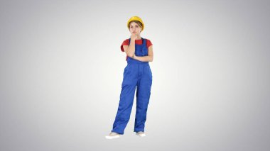 Woman in construction uniform listening to instructions on gradient background.