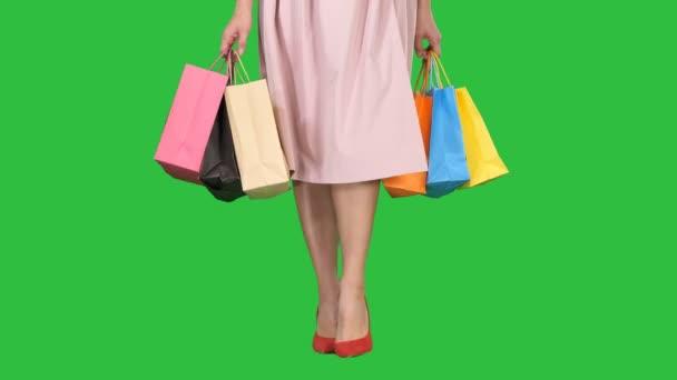 Fiatal nő lába könyv színes bevásárló táskák, a zöld képernyő, Chroma Key.
