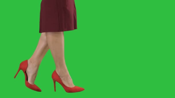 Sexy woman legs in red heels walking Business lady on a Green Screen, Chroma Key.