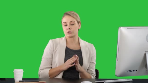 Lady looking and talking to camera at her work desk and pointing to the sides on a Green Screen, Chroma Key.