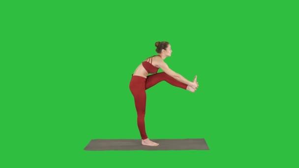 Celou délku zastřelil. Krásná mladá fit žena v sportovní dělá cvičení, ohýbání variace Utthita Hasta Padangusthasana, Dandayamana-Janushirasana na zelené obrazovce, Chroma Key