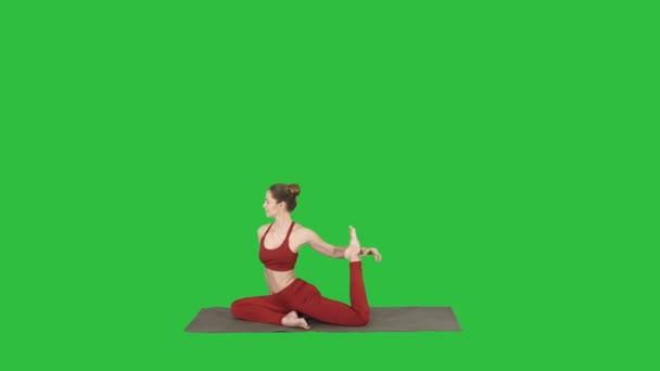 Krásná mladá žena nosí červené sportovní dělá jógu nebo pilates cvičení jeden Legged král holuba představovat, Eka Pada Rajakapotasana na zelené obrazovce, Chroma Key