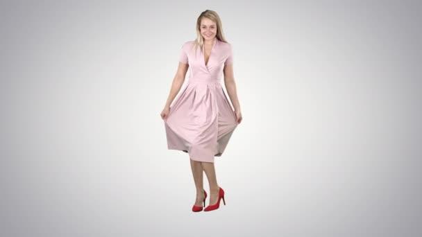 Frau in rosa Kleid dreht sich um und sieht sich selbst an wie im Spiegel auf dem Hintergrund des Gefälles.