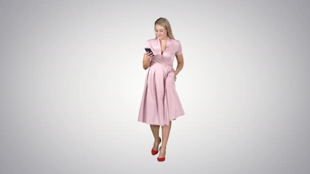 Mladá žena v růžové při pohledu na mobilní smartphone a textové něco při chůzi na gradient pozadí.