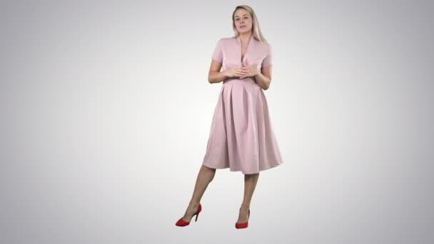 glückliche blonde Frau in rosa im Gespräch mit der Kamera und zeigt auf die Seite auf dem Hintergrund des Gefälles.