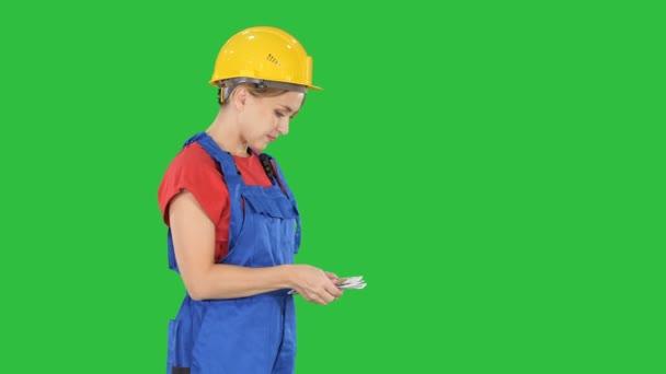 Mladá žena inženýr nebo architekt držící bankovky euro plat na zelené obrazovce, Chroma Key.