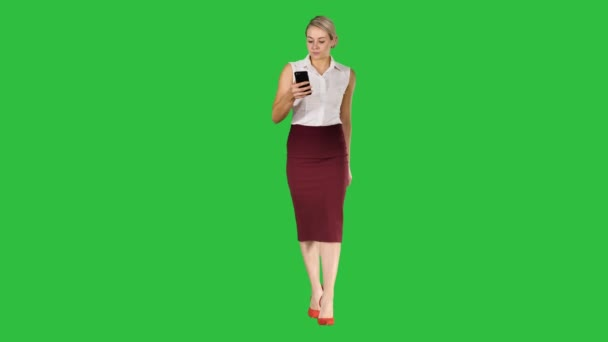 Excited woman walking and reading amazing news on line in a smart phone on a Green Screen, Chroma Key.
