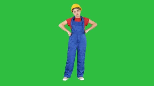 Naštvaná žena stavební dělník ukazuje pěst negativní agresivní emoce na její obličej na zelené obrazovce, Chroma Key.