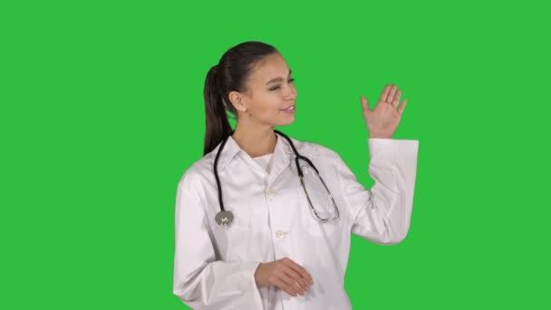 Ženský lékař něco s rukama ukazuje rozšířené prezentace na zelené obrazovce, Chroma Key.