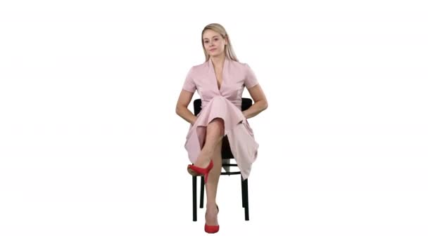 Beautiful young woman, girl, model blonde with long hair sitting on a chair and looking to camera on white background.