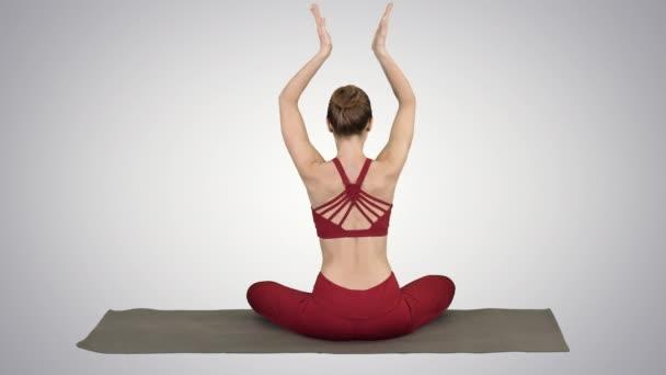 junge sportliche Frau sitzt in Lotus-Pose, die Hände über dem Kopf auf Steigungshintergrund.