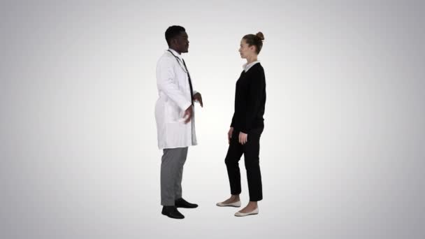 Male doctor offers medication to young woman on gradient background.