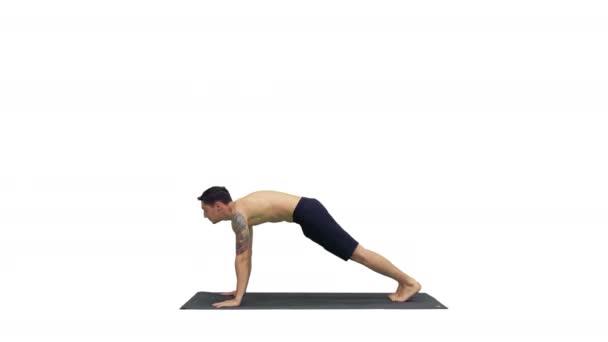 Profil eines muskulösen, gut aussehenden jungen Mannes beim Training, der in Yoga-Haltung nach oben, nach unten gerichteter Hundehaltung steht und dann seine Arme auf weißem Hintergrund ausstreckt.