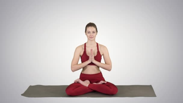 Beautiful young woman sitting in yoga pose Lotus changing position of her hands on gradient background.