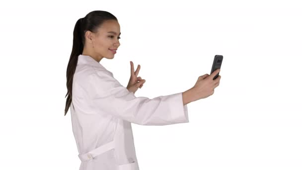 Stylish european doctor brunette taking selfie on phone while walking on white background.
