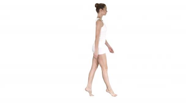 A fiatal nő séta neki tip lábujjait, fehér háttér.