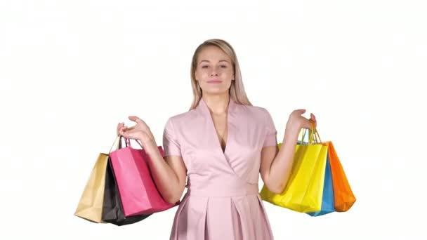 Nákupní žena šťastný úsměv držení nákupních tašek iwhile chůze na bílém pozadí.