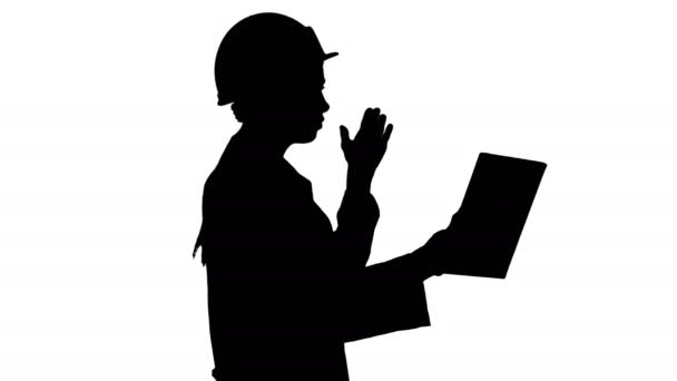 Silhouette Woman engineer with tablet making video call.