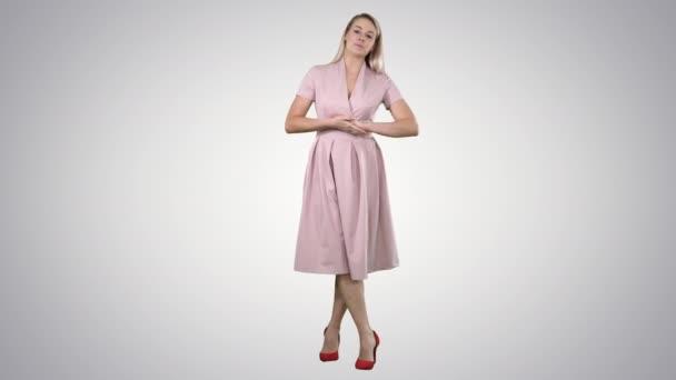 Po celé délce portrét. Roztomilá dívka plná délka v růžových šatech mluví do kamery a usmívá se na pozadí s přechodem. Profesionální snímek v rozlišení 4 k. 005. můžete použít ji například v komerční video