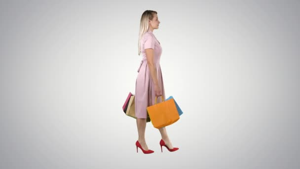 Happy pretty girl holding walking with shopping bags on gradient background.