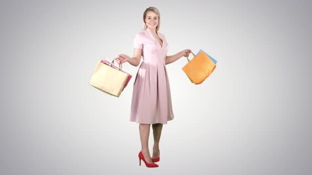 Šťastná mladá žena dělat zase s nákupní tašky v ruce při pohledu na fotoaparát na pozadí s přechodem.