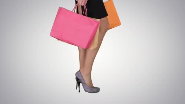 Chůzi nohy nákupní lady s nákupní taškou na pozadí s přechodem.
