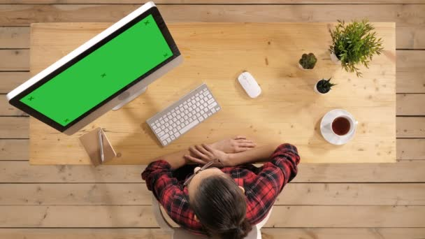 Young surprised enthusiastic woman sitting in front of computer. Green Screen Mock-up Display.