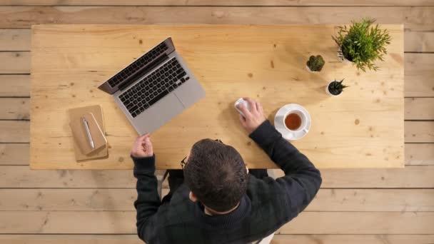 Pocit únavy. Frustrovaný mladík pohledný hledá vyčerpaná přitom sedí u svého pracovního místa a nošení brýlí v ruce.