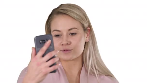 Smiling young blonde girl taking a selfie on white background.