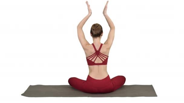 Junge sportliche Frau sitzt in Lotus-Pose, die Hände über dem Kopf auf weißem Hintergrund.