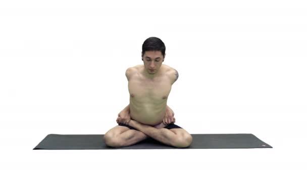 Mladý muž cvičí jógu v lotosové pozici na bílém pozadí.