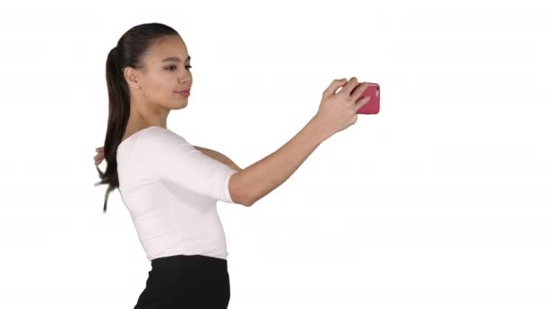 Pretty girl taking a selfie and walking on white background.